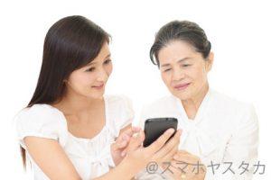 老母にスマホを教える女性